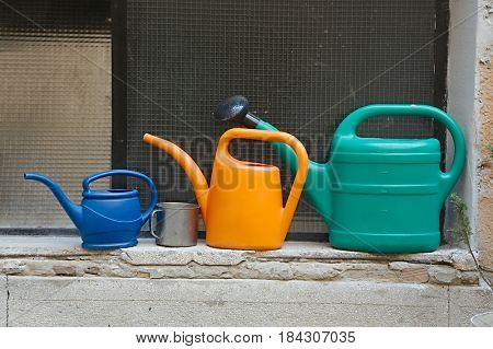 Different watering cans on a windowpane