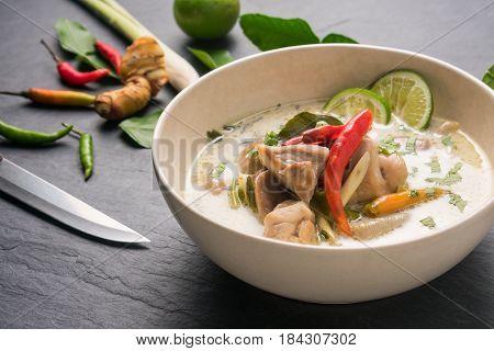 Chicken coconut soup (Tom Kha Gai) Thai food on black stone table background