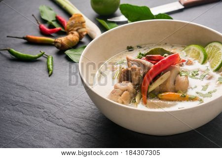 Chicken coconut soup (Tom Kha Gai) Thai food on black stone table background