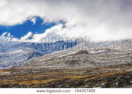 Mountains Covered In Snow Under Fluffy Clouds Landscape