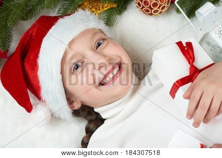 child girl having fun with christmas decoration, face expression and happy emotions, dressed in santa hat, lie on white fur background, winter holiday concept
