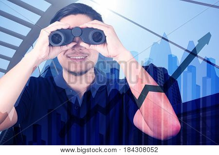 Double Exposure Of Asian Investor With Binoculars. Over Abstract Urban Background With Financial Gra