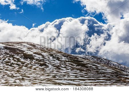 Snow Patches On Mountains And Fluffy Clouds On Bright Sunny Day
