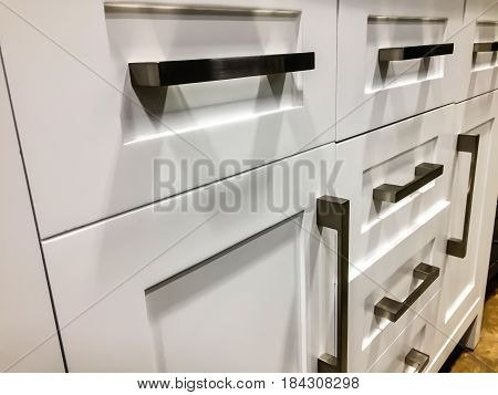 White kitchen cabinets. Modern base cabinets with chrome cabinet handles. Modern Cabinets. Contemporary Italian kitchen cabinet design. Base doors and drawers of wooden kitchen cabinet.