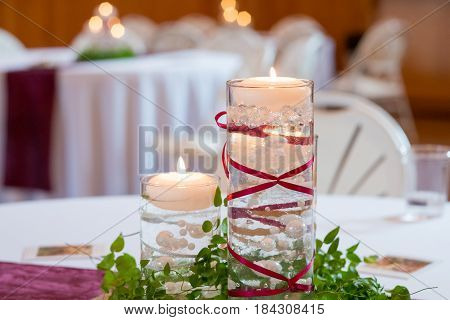 Candles are used for decor at this wedding reception that features very beautiful decorations.