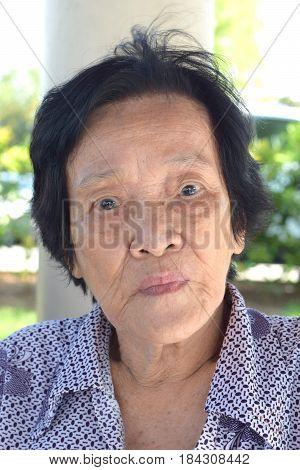 A sad looking elderly asian woman looking at camera