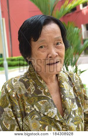 A happy looking asian elderly woman posing outdoor
