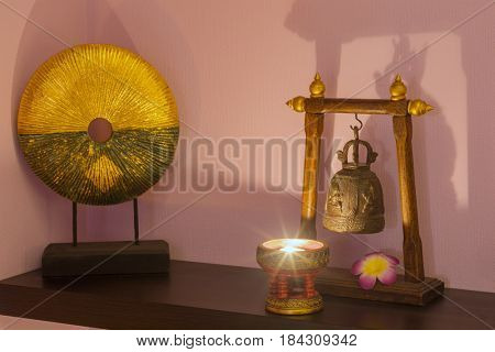 Asian decorations are on table - candlestick, small gong and bell