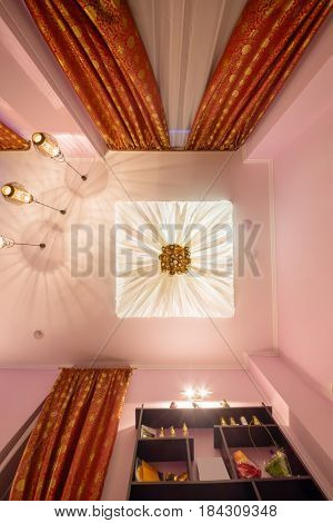 White canopy hanging from ceiling with ornate decoration in room, under view