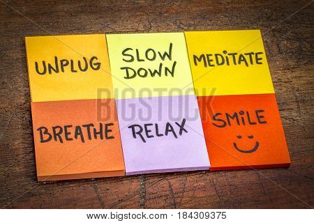 unplug, slow down, meditate, breathe, relax, and smile motivational lifestyle reminders on colorful sticky notes against grunge wood