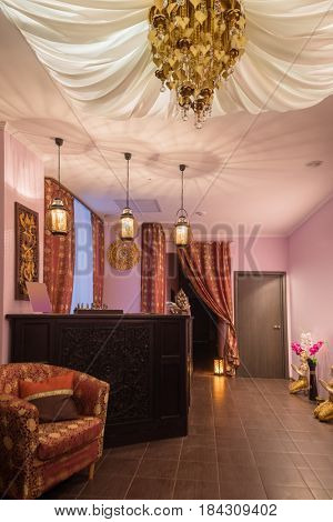 Wooden reception with carving in thai day spa with asian decoration and canopy