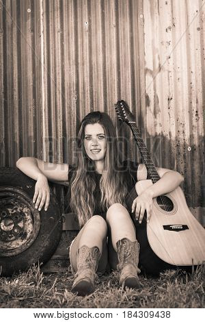 Beautiful smiling country girl with guitar