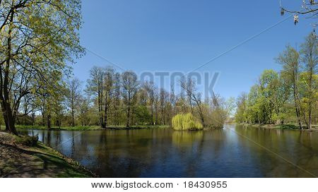 Park and the lake in spring time. Panoramic wide, sunny weather view with people walking. Faces not recognizable.