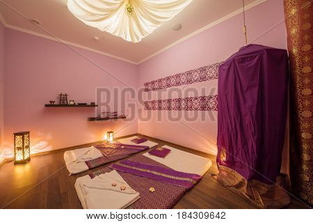 Empty beautiful cozy room with mats for thai massage and curtain dressing