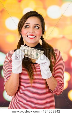 Closeup portrait of female clown mime holding a twenty dollar bill asking for money