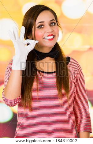 Closeup portrait of happy female clown mime gesturing all right