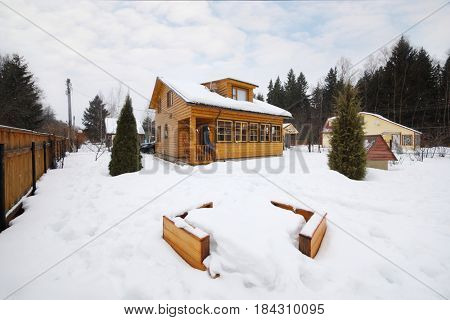 Cozy wooden country cottage with playground among snow at winter day