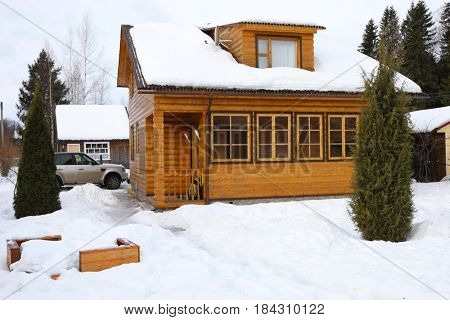 Wooden country cottage among snow, car near it at winter day