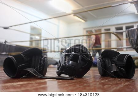 Boxing helmet and gloves are on floor and people on ring out of focus on boxing club