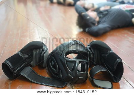 Boxing helmet and gloves are on floor and trainig people out of focus on boxing club