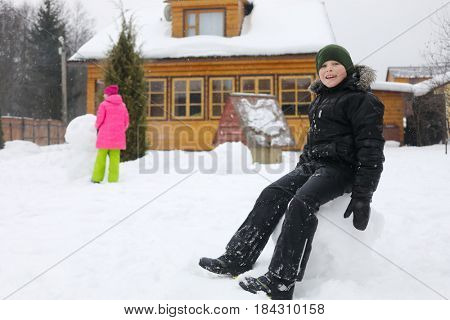 Boy sits in big snowball, girl makes snowman near wooden country house during snowfall at winter day, girl out of focus