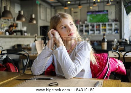 Pretty girl sits at table in cozy stylish cafe, looks away and dreams