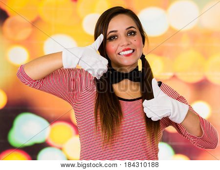 Closeup portrait of cute young girl clown mime smiling holding thumbs up