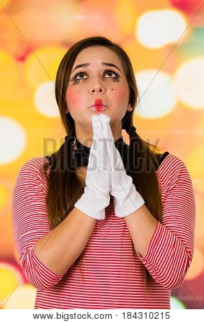 Closeup portrait of cute young girl clown mime praying, begging