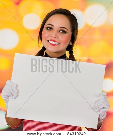 Closeup portrait of cute young girl clown mime holding white paper, copy space