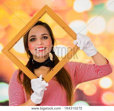 Closeup portrait of cute happy young girl clown mime holding wooden frame in front of her face