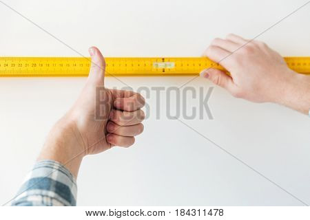 Close up man showing thumb up and using ruler isolated