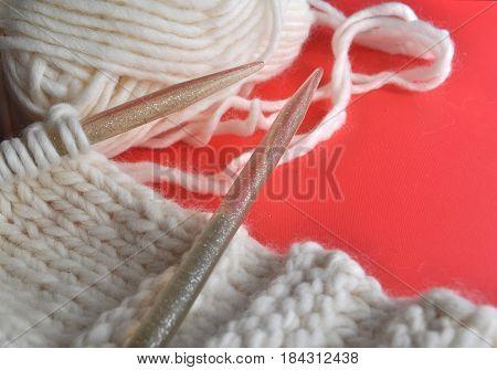 White wool knitting needles and handmade knits on bright orange background