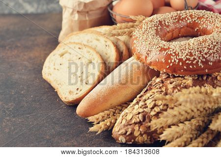 Various bread and wheat on brown background rustic food concept