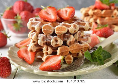 Sweet waffles with strawberries and powdered sugar on a white background