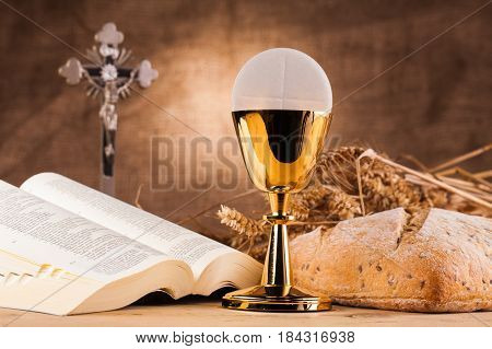 holy communion next to bible on top of wooden table