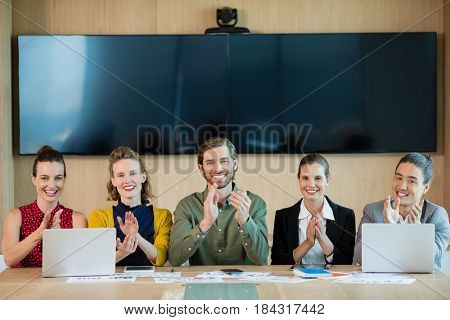 Portrait of smiling business team applauding during meeting in conference room at office