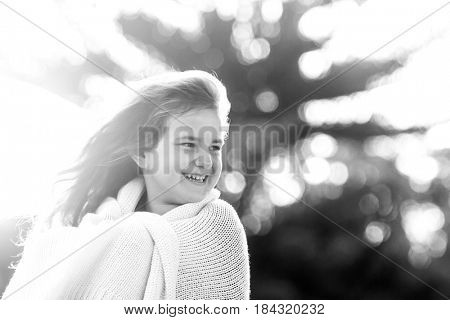 outdoor black and white portrait of young happy smiling child girl wrapped in blanket