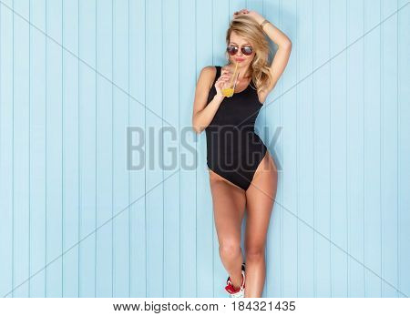 Young sexy woman drinking juice or cocktail in bodysuit with perfect body wearing sunglasses.