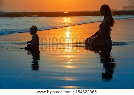 Family swimming fun on black sand beach with sea surf. Happy mother baby son sit and look at ocean on sunset sky with sun background. Child with parents activity healthy lifestyle on summer holiday.