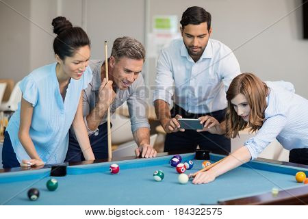 Business executive taking picture with mobile phone while colleagues playing pool in office space