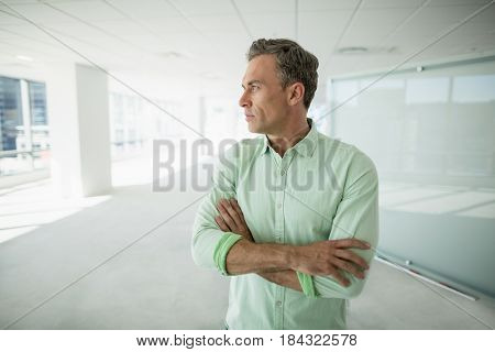 Thoughtful business executive standing with arms crossed in office corridor