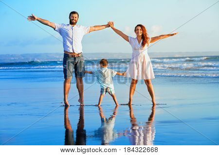 Happy family - father mother baby son hold hands walk and jump together by water pool on sunset black sand beach with sea surf. Travel active lifestyle parents with child on summer vacation.
