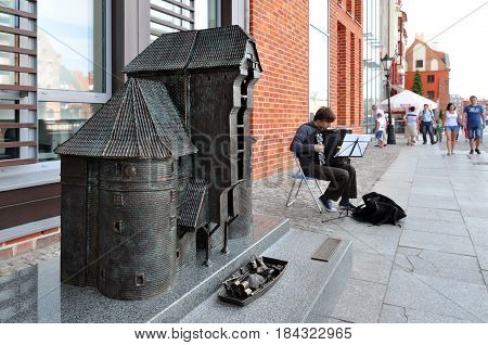 Gdansk, Poland - July 13, 2013: Metal sculpture of the old crane in Gdansk. Street musician on the background.