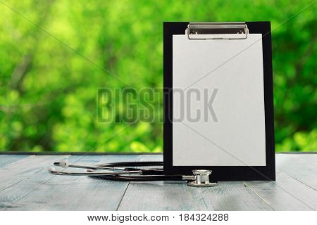 Black clipboard with stethoscope on a blue wooden table against the background blur green leaves bokeh