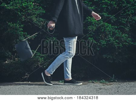 Fashionable woman wearing a black coat jeans sneakers and black handbag. Spring fashion outfit