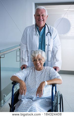 Portrait of doctor holding senior patient on wheelchair in passageway at hospital