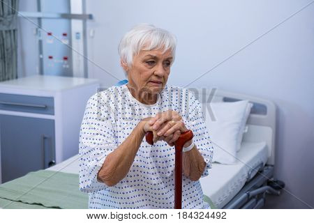 Worried senior patient sitting on bed with walking stick at hospital