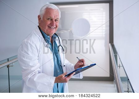 Portrait of doctor writing on clipboard in the passageway