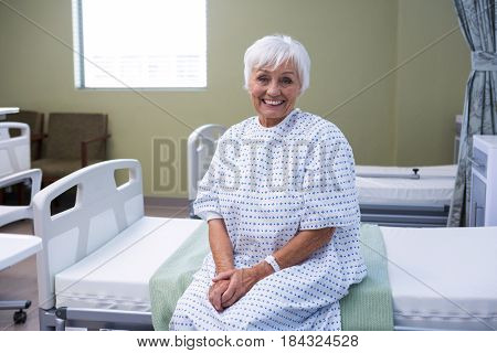Portrait of smiling senior patient sitting on bed in hospital