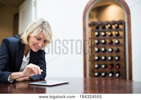 Smiling businesswoman using digital tablet in a restaurant